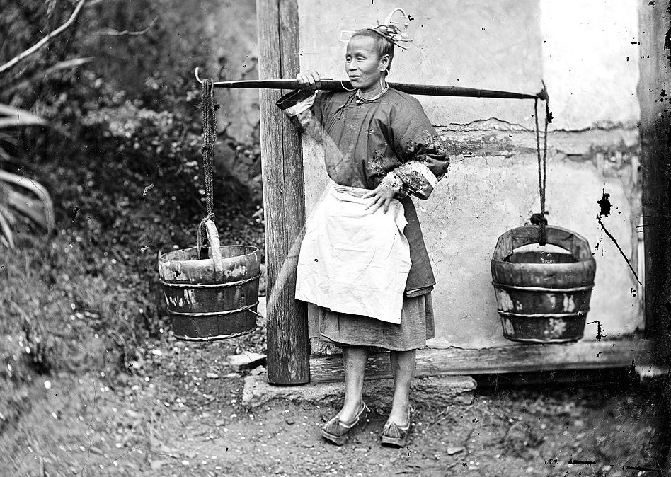 A woman carrying buckets of night-soil